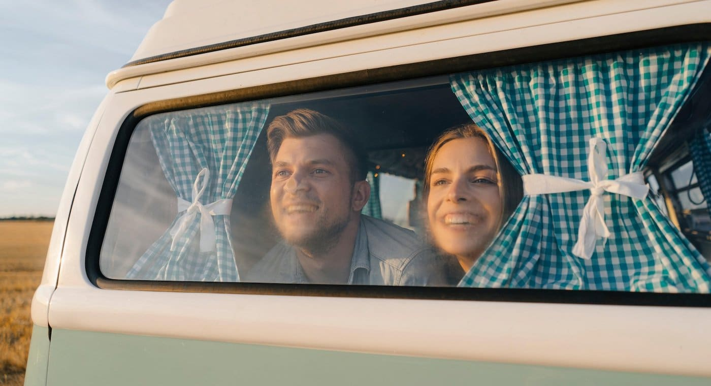 RGNATH Happy young couple leaning against window of a camper van